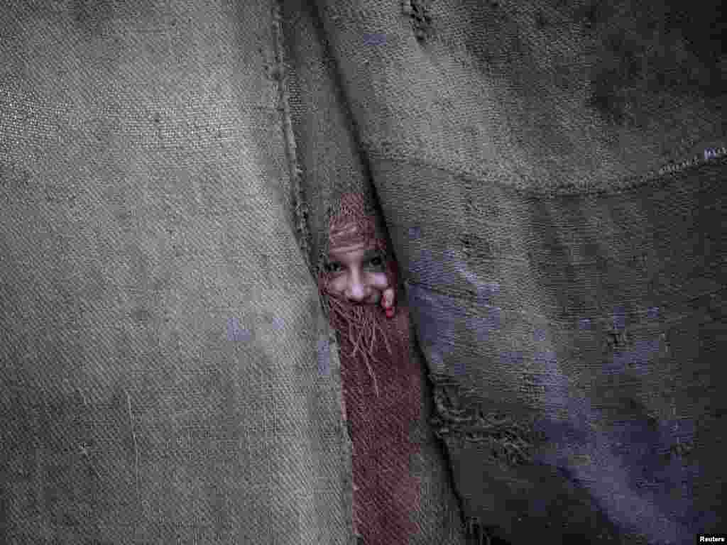 A Pashtun girl peeps through a jut sack from the doorway to her family dwelling in Peshawar, Pakistan on June 1. Photo by Fayaz Aziz for Reuters
