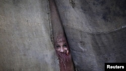 A Pashtun girl peeks through the doorway to her family dwelling in Peshawar.