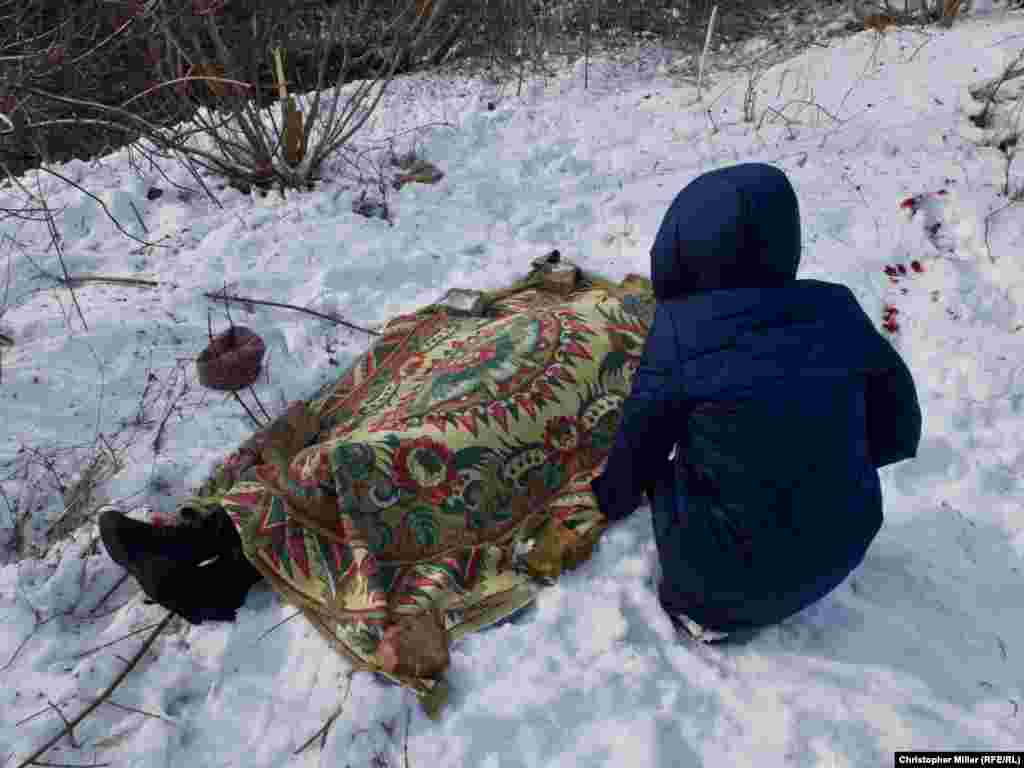 Nadia Volkova leans over the body of her mother, Katya, who was killed during shelling in the eastern Ukrainian city of Avdiyivka on February 1. (RFE/RL/Christopher Miller)