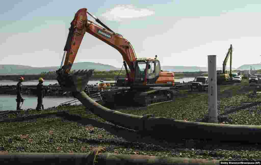 This photo released by Greenpeace on June 28 shows an excavator disassembling a pipe from a Norilsk Nickel enrichment plant that was draining water into a river. The company said that it improperly pumped wastewater into the Arctic tundra and that it has suspended the employees responsible for the error.