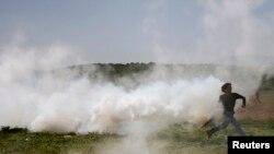 Македония полициясы бозгундарды карай көздөн жаш агызчу газ менен аткан учур. 13-апрель, 2016-жыл