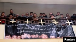 Neighbors and friends of the relatives of Egyptian Coptic men killed by Islamic State militants in Libya attend mass as a banner with pictures of the men who were killed is displayed on the church wall in El-Our village in Egypt's Minya governorate on February 16.