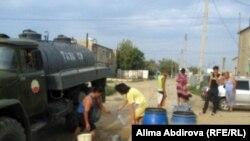 Местные жители запасаются привозной питьевой водой. Поселок Кенкияк Актюбинской области, 11 июля 2011 года.