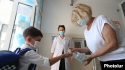 Armenia -- A teacher pours disinfecant onto the hands of a student entering a private school in Yerevan, September 1, 2020.