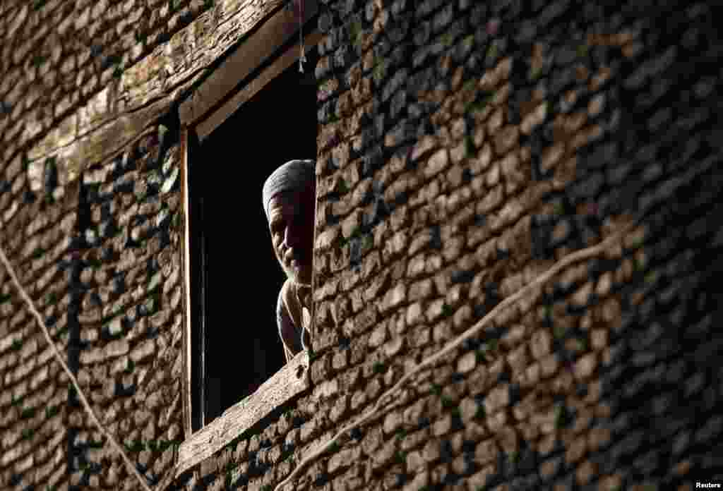 A Kashmiri man looks through the window of his house in downtown Srinagar. (Reuters/Danish Ismail)