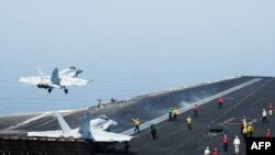 """A U.S. Navy handout photo obtained on August 8 shows sailors directing aircraft as an F/A-18E Super Hornet attached to the Tomcatters of Strike Fighter Squadron (VFA) 31 takes off from the flight deck of the """"USS George H.W. Bush"""" after President Barack Obama authorized air strikes against Islamist militants in Iraq and humanitarian aid airdrops."""