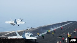 "A U.S. Navy handout photo obtained on August 8 shows sailors directing aircraft as an F/A-18E Super Hornet attached to the Tomcatters of Strike Fighter Squadron (VFA) 31 takes off from the flight deck of the ""USS George H.W. Bush"" after President Barack Obama authorized air strikes against Islamist militants in Iraq and humanitarian aid airdrops."