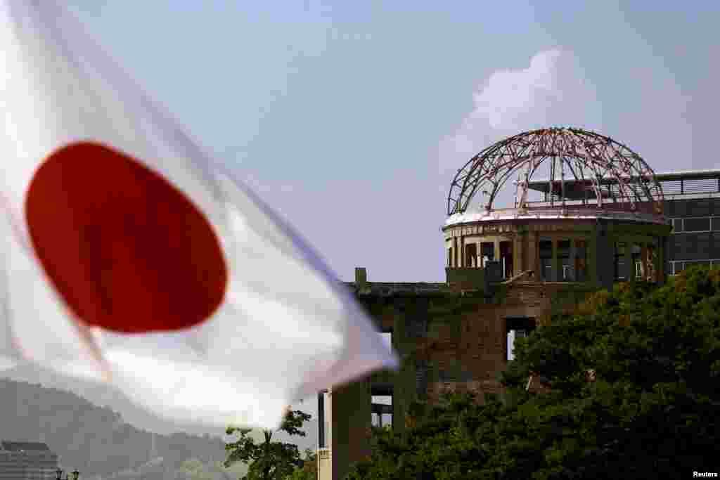 """Флаг Японии на фоне """"Атомного купола"""" (""""Купола Гэмбаку""""), внесенного в список Всемирного наследия ЮНЕСКО."""