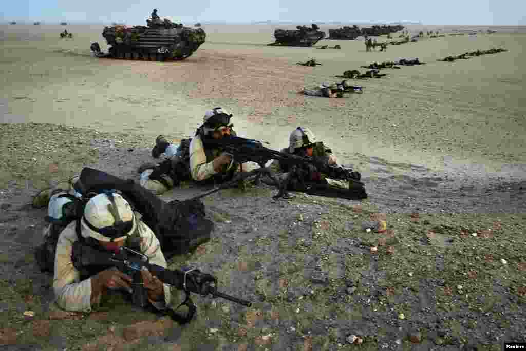 U.S. Marines in combat gear take their positions during a last-minute exercise in northern Kuwait near the border with Iraq on March 18, 2003.