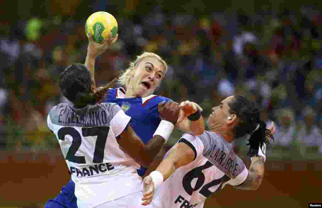 Anna Sen of Russia (center) and Estelle Nze Minko and Alexandra Lacrabere of France in action in the women's handball final. Russia brought home its first-ever Olympic gold medal in the sport after defeating France 22-19.