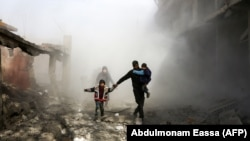 Syrian civilians flee from reported regime air strikes in the besieged Eastern Ghouta region on the outskirts of the capital, Damascus, on February 8.
