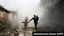 Syrian civilians flee from reported regime air strikes in the rebel-held town of Jisreen, in the besieged Eastern Ghouta region on the outskirts of the capital, Damascus, on February 8.
