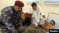 A wounded army recruit is transferred to a hospital after a bomb attack in Baghdad today.