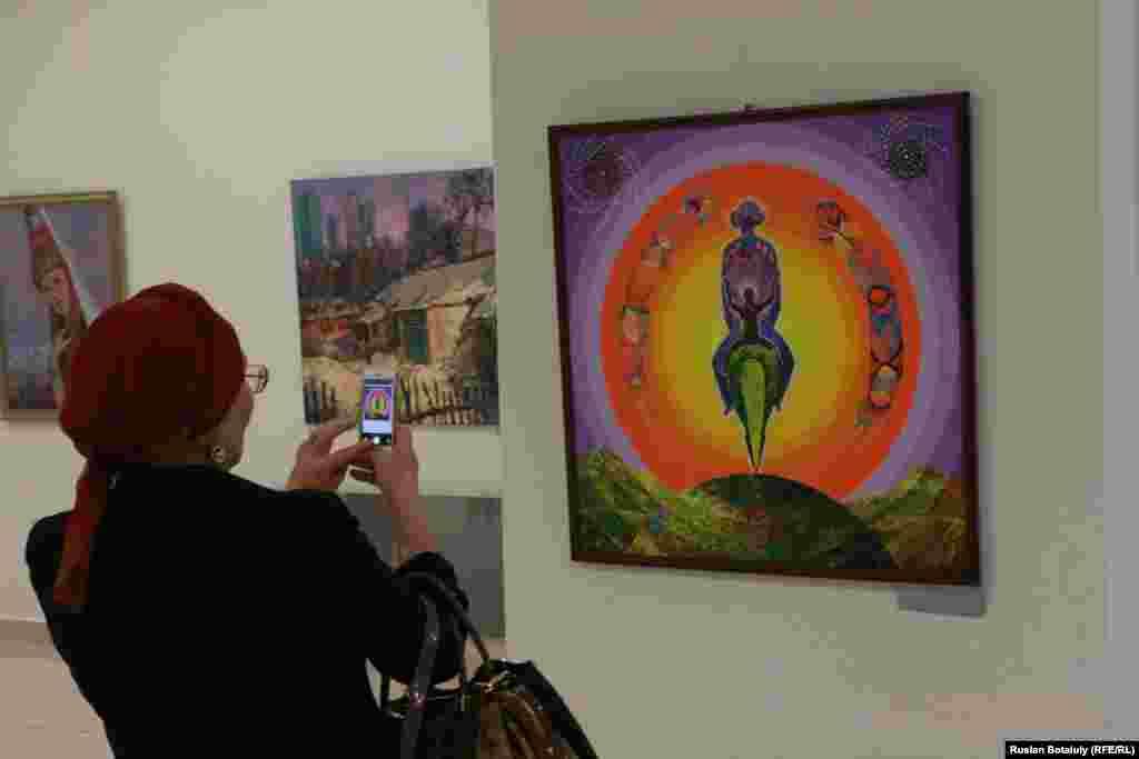 Женщина фотографирует на свой мобильный телефон картину Бахтыбека Талкамбаева «Нурлы жол».