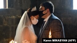 ARMENIA -- A bride and a bridegroom wearing protective face masks exchange kisses during a wedding ceremony in a church in Saghmosavan village on June 14, 2020.