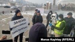 Активист Жанболат Мамай (с плакатом) проводит одиночный пикет. Алматы, 15 января 2021 года.