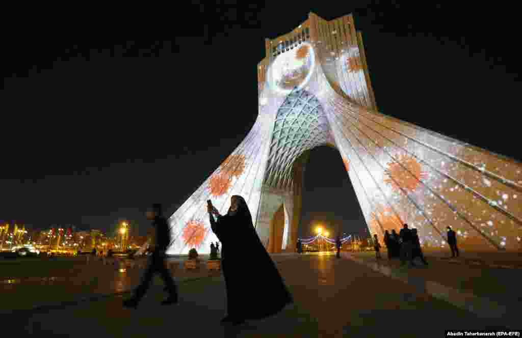 People walk past Tehran's Azadi Tower, which has been lit up with messages of hope in solidarity with all the countries affected by the COVID-19 pandemic. (epa-EFE/Abedin Taherkenareh)