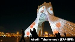 People walk past Azadi (Freedom) Tower lit up with messages of hope in solidarity with all the countries affected by the COVID-19 coronavirus pandemic, in Tehran, March 31, 2020