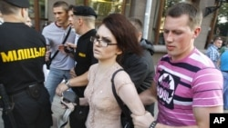 A woman is detained by Belarusian plainclothes policemen during one of the weekly protests against the regime in July.