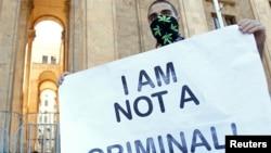 Адамды есірткі тұтынғаны үшін қылмыстық жауапқа тартуға қарсылық білдіруші жігіт наразылық акциясында тұр. Тбилиси, 2 маусым 2013 жыл.