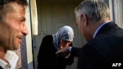 زن سوری در حال بوسیدن دست ژان-مارک ارو، وزیر خارجه فرانسه در اردوگاهی در جنوبشرقی ترکیه.