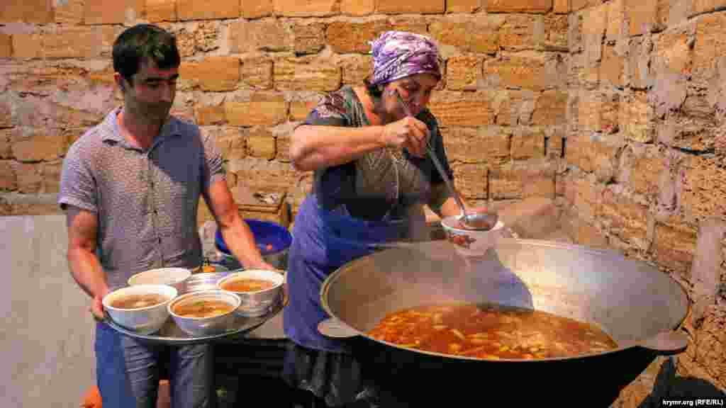 После этого все перемещаются за стол. Помощники разносят горячие блюда с едой