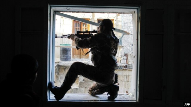 A member of Liwa Salahadin, a Kurdish military unit fighting alongside rebel fighters, aims at a regime fighter in the besieged district of Karmel al-Jabl in eastern Aleppo on December 6.
