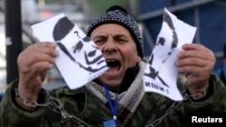 A protester tears a portrait of President Viktor Yanukovych.