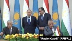 Президент Казахстана Нурсултан Назарбаев и президент Таджикистана Эмомали Рахмон (справа) наблюдают за ходом подписания документов министрами иностранных дел двух стран. Душанбе,14 сентября 2015 года.
