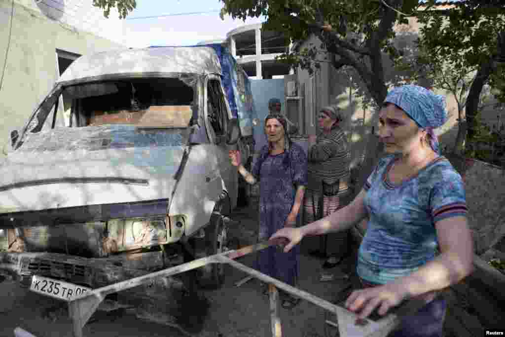 Local residents stand near a mini truck, which was seriously damaged during a special antiterrorist operation conducted by Russian military forces in the town of Kaspiysk in July.