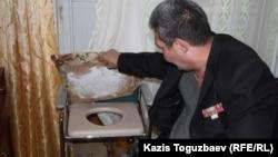Бауыржан Джасымбеков показывает кресло с отверстием в сиденье.