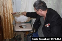 Бауыржан Жасымбеков тесігі бар креслоны көрсетіп жатыр.