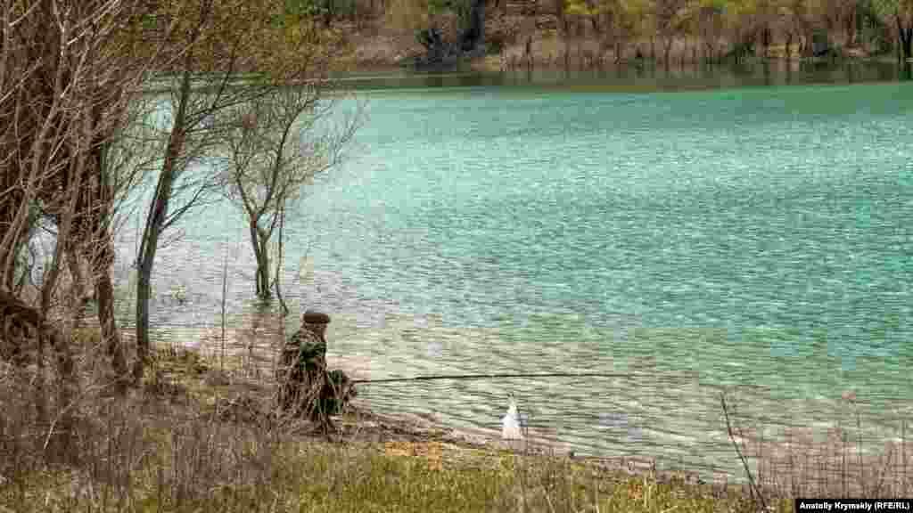 Одинокий рибалка на березі водосховища