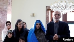 "Afghan President Ashraf Ghani (R) speaks to the media after Sharbat Gula (2nd R), the green-eyed ""Afghan Girl"" whose 1985 photo in National Geographic became a symbol of her country's wars. She arrived in Kabul on November 9."