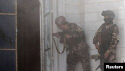 Afghan security forces take position at the scene of an attack on the Indian consulate in Herat.