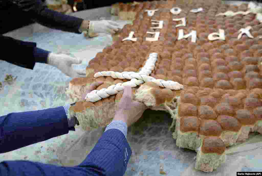 People break traditional Christmas bread to mark the Orthodox Christmas Day festivities in Belgrade, Serbia, on January 7. Children traditionally scramble for a piece of the bread, searching for a gold coin hidden inside. (AP/Darko Vojinovic)