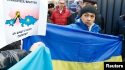 "Kazakhs protest outside the Consulate-General of Russia in Almaty on March 3, supporting Ukraine ""for your and our freedom."""