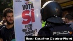 """Сторонник независимости Каталонии с плакатом """"Проголосуй за """"Да"""" перед испанским полицейским. Барселона, 20 сентября 2017 года"""