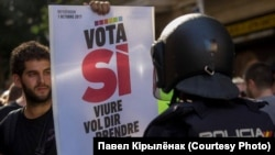 """Сторонник независимости Каталонии с плакатом """"Проголосуй за """"Да"""" перед испанским полицейским. Барселона, 20 сентября"""