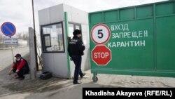 Полицейский у ворот административного здания, закрытого на карантин. Семей, 13 апреля 2020 года