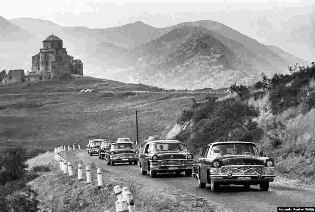 A convoy of Soviet Chaika cars glide along a road near Tbilisi, Georgia. The Chaika ('Seagull') was one of several Soviet cars that were copied nearly wholesale from their Western forerunners.