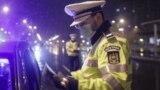 Un polițist, verificând documente, după instalarea restrcițiilor de circulație