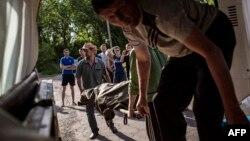 Чоловіки вантажать мертве тіло убитого українського солдата у бою у Воловасі, 22 травня 2014 року