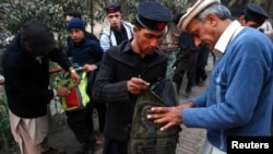 Students get their bags checked by school security staff at a school after it reopened in Peshawar in January.
