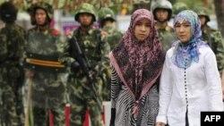 Екі ұйғыр қызы Қытай полициясы қоршауға алған аймақтан өтіп барады
