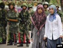 Две мусульманки проходят мимо вооруженных солдат. Урумчи, 14 июля 2009 года.