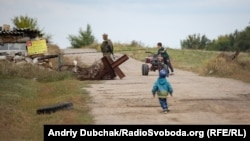 Ten-year-old Davyd rides a mini-quad bike while Stepan tries to catch up. Children are not permitted to go beyond the Luhanske checkpoint.