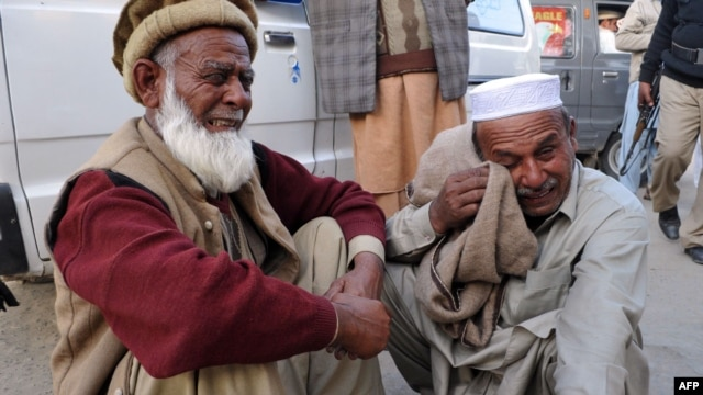 Men react after learning that their relatives were among those killed in the bomb blast in Nowshera.