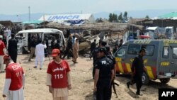 Pakistani security and medical personnel are pictured at the site of a car-bomb attack at the Jalozai refugee camp near Peshawar on March 21.