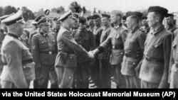 Фото 1942 року, надане прокуратурою Гамбурга Музею пам'яті Голокосту в США. Гіммлер потискає руку новим охоронцям концтабору «Травники»